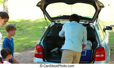 Father emptying the trunk of the car with his family