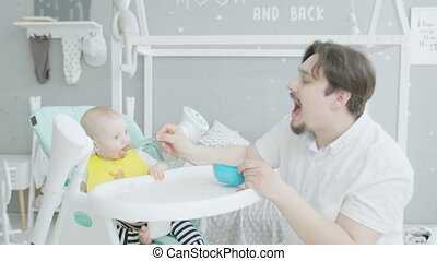 Father feeding baby sitting on high chair at home
