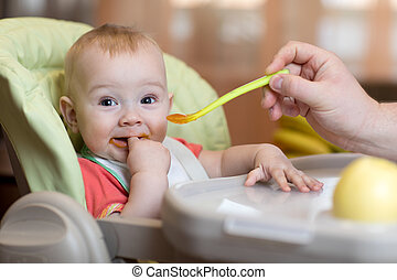 father feeding baby with spoon