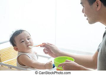 Father feeding child food.