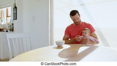 Father feeding his baby boy with spoon 4k - Father feeding...