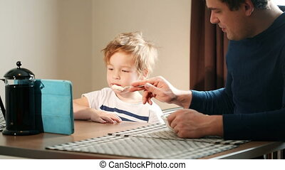 Father feeding his son while he watching cartoons on pad