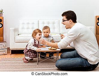 father feeding kids