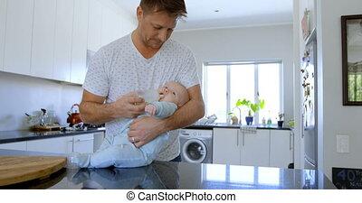 Father feeding milk to his baby boy in kitchen 4k