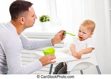 Father feeds the cry baby son