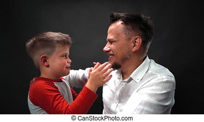 Father give high five to his boy son and hug him tight is slow motion in studio isolated on dark gray or black background. Overjoyed young adult with his cute child son. High definition footage.