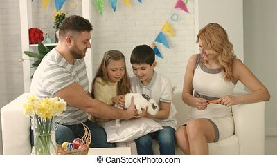 Father gives children a rabbit for Easter and they stroke it