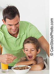 Father giving cereal to his son in the kitchen