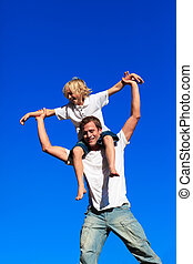 Father giving his son a piggyback ride against the blue sky