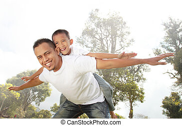 father giving his son piggyback ride outdoors