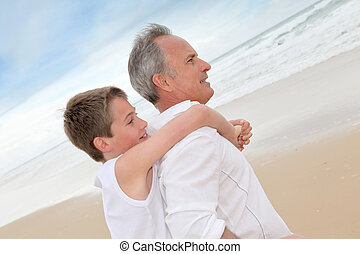 Father giving piggyback ride to son at the beach