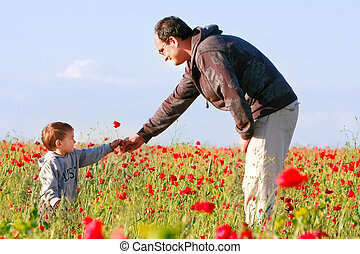 father giving poppy flower to his son