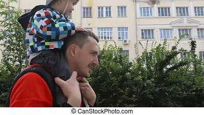 Father giving son piggyback ride on his shoulders
