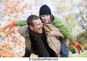 Father giving son piggyback