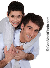 father giving young son piggyback