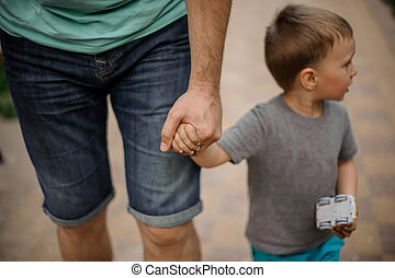 Father hand holding a little hand of his son