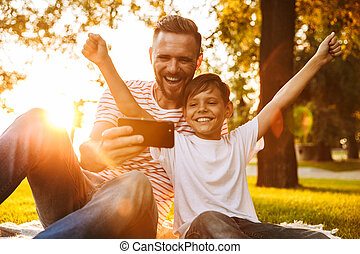 Father have a rest with his son outdoors in park play games with mobile phone.