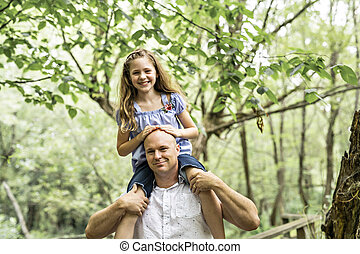 Father having fun in forest with his daughter on his shoulder