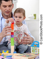 Father helping daughter to build towel from wooden blocks