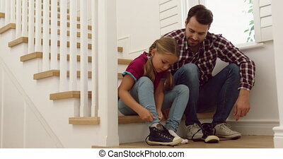 Father helping her daughter to wear shoes on stairs in a comfortable home 4k