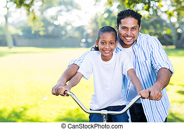 father helping his daughter ride a bike