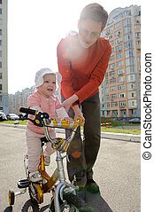 Father helping his daughter riding bicycle