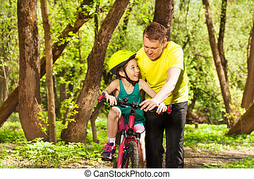 Father helping his daughter to ride the bicycle