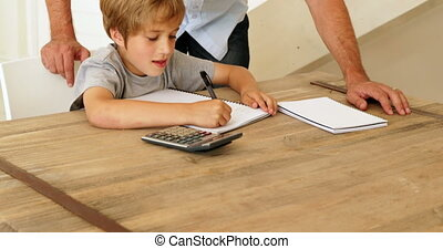 Father helping his son with his math - Father helping his...