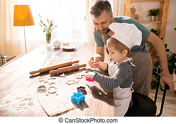 Father helping little son to make shortbread