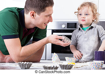 Father helping son baking muffins