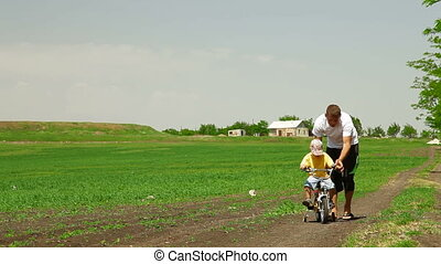 Father Helping Toddler Ride Bicycle