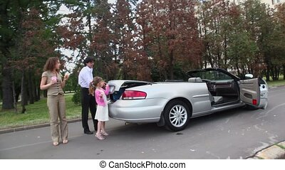 Father helps girl to open boot of cabriolet, mother eats