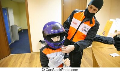 Father helps son to dress on in uniform for go-cart racing