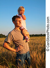 Father hold daughter on shoulder on wheat field