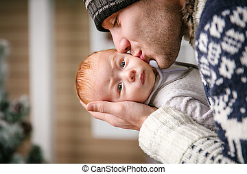 Father holding and kissing baby son