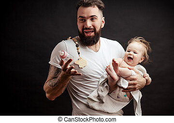 Father holding and taking care of little infant baby, feeding from bottle.
