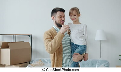 Father young man is holding daughter in hands showing key to new apartment smiling enjoying relocation. Family and accommodation concept.