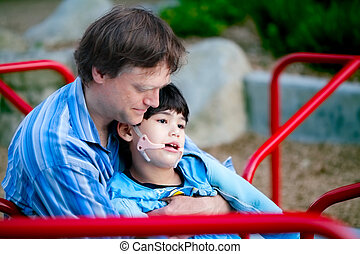 Father playing with disabled son on merry go round at playground. Child has cerebral palsy.