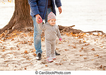 Father holding hands with small daughter on beach