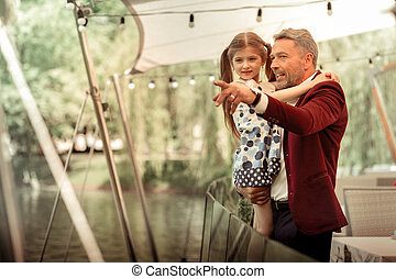 Father holding his daughter while looking at ducks in lake