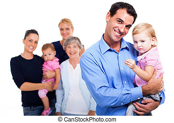 father holding his daughter with extended family on background