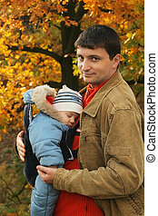 father holding his son in baby carrier