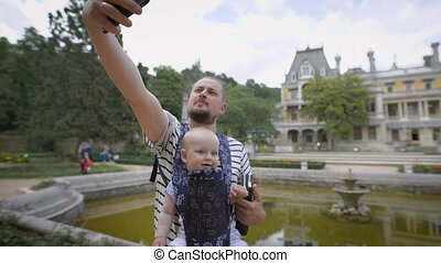 Father holding his young son and makes selfie phone. They travel together