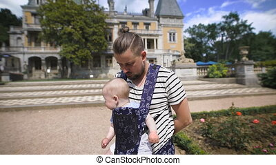 Father holding his young son. They travel together