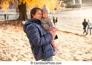 Father holding little daughter on hands at beach