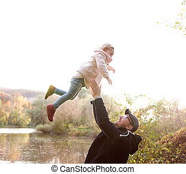 Father holding little daughter, throwing her in the air -...