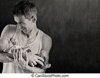 Father holding newborn baby, over dark background