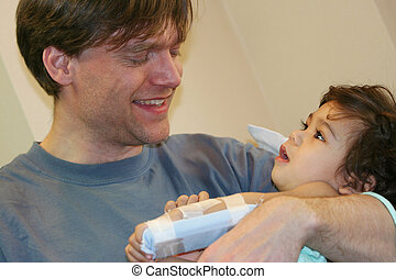 Father holding sick baby in hospital