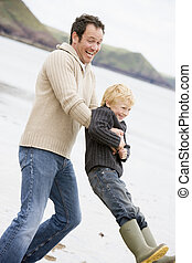 Father holding son at beach smiling