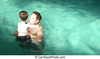 Father Holding Son in Swimming Pool